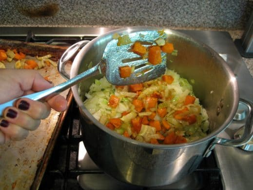 metal spatula transferring roasted fennel and sweet potato to soup pot of cabbage and onion