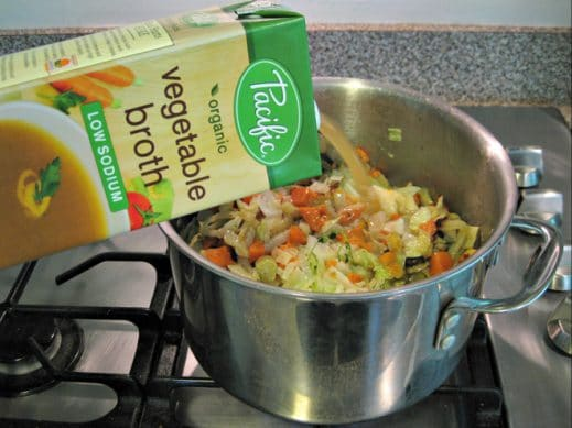 adding organic vegetable broth to soup pot of vegetables