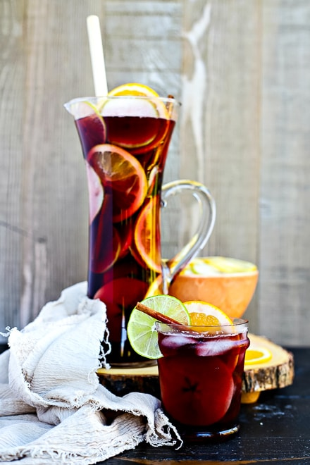 large glass pitcher of fall sangria with sliced fruit