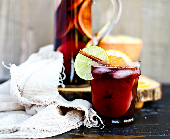 pitcher of fall sangria with cut orange and frayed linen