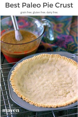 baked paleo pie crust sitting on a wire cooling rack with pumpkin pie filling and linen in the background