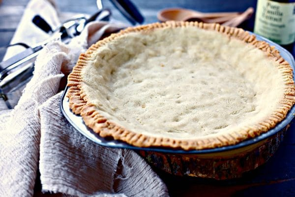 baked paleo pie crust with wood measuring spoons in the background