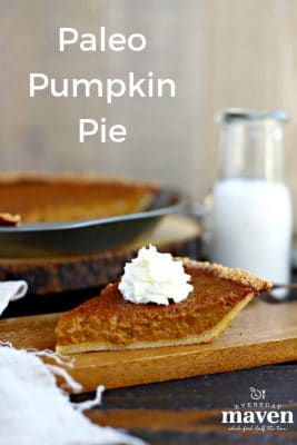 slice of pumpin pie topped with whipped cream on a wood cutting board in front of whole pie with glass of milk in glass jar
