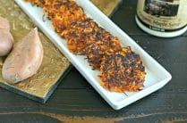 thin white rectangle dish filled with cooked sweet potato latkes on a gold tray next to a bottle of maple syrup and raw sweet potatoes