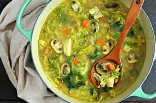 large soup pot with easy turkey soup with cabbage and turmeric with wood ladle and beige linen