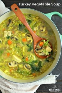 large soup pot with easy turkey soup with cabbage and turmeric with wood ladle and beige linen with text for pinterest