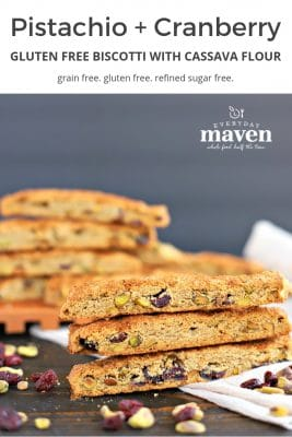 stacks of gluten free biscotti on a beige linen with cranberries and pistachios scattered on the table