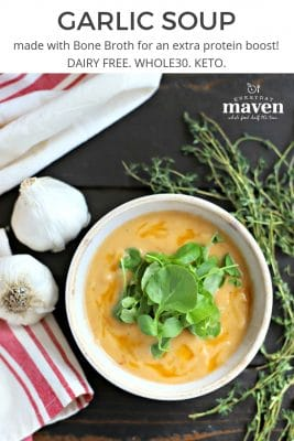 rustic bowl filled with creamy garlic soup topped with watercress leaves. on wooden table with fresh thyme, whole heads of garlic and a red and white linen