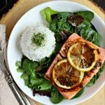 overhead view of white plate with cooked salmon with lemon slices, white rice and salad dressed with balsamic vinaigrette