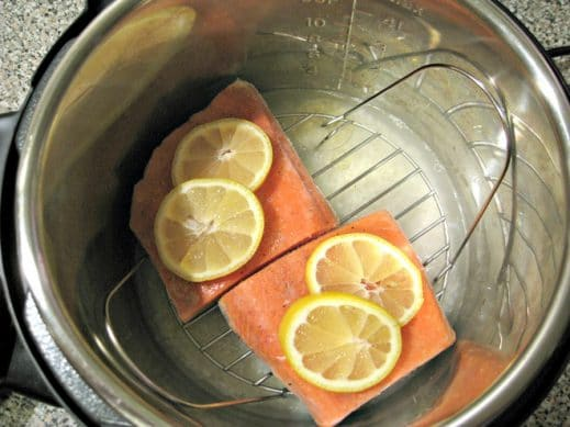 looking into Instant Pot filled with uncooked rice, watern and steaming rack over it with frozen salmon topped with sliced lemo
