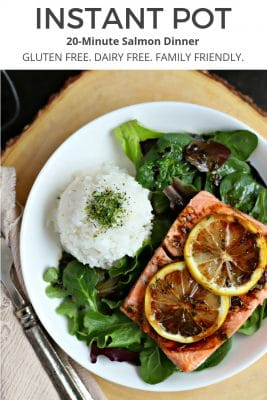 close up of white plate with bed of mixed greens, cooked salmon topped with sliced lemon and ball of white rice topped with spinach seasoning. balsamic dressing drizzled on top of salmon and salad