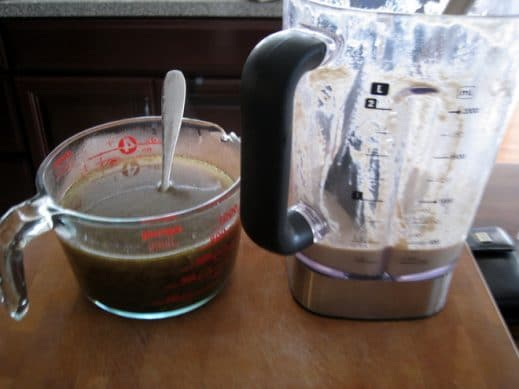 canister of high-speed blender with dairy-free creamy mushroom sauce alongside pyrex of leftover mushroom broth with silver spoon sticking out on a wood cutting board