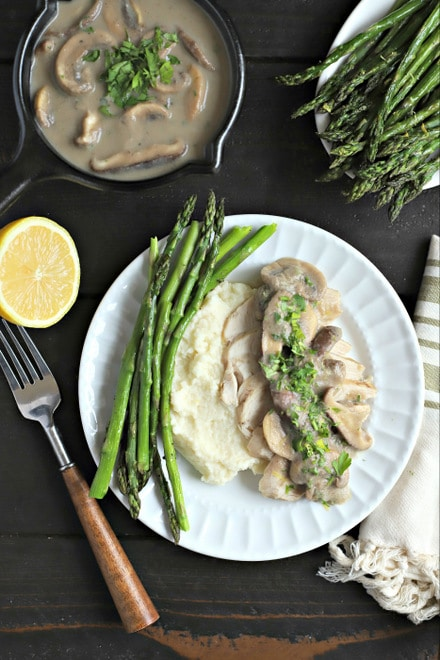 white dinner plate with asparagus, mashed cauliflower and poached chicken breast with creamy mushroom sauce alongside a cut lemon, flatware with wood handles and a small cast iron pot of more mushroom sauce