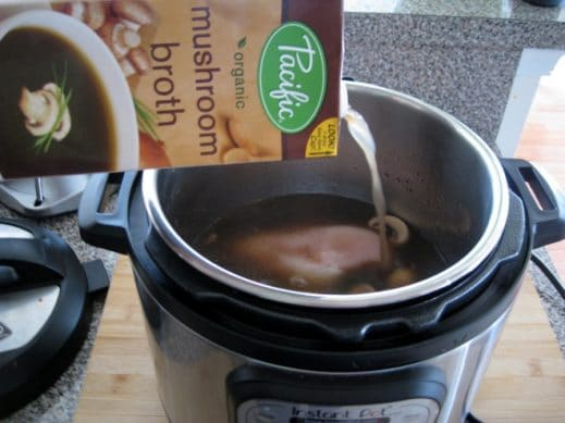 adding mushroom broth to an InstantPot with uncooked chicken breasts for poached chicken breast