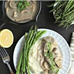 white dinner plate with asparagus, mashed cauliflower and instant pot poached chicken breast with creamy mushroom sauce with text on top for Pinterest