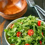 close up of arugula salad in a white bowl with wood serving bowls in the background