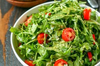 close up of white serving bowl with arugula salad