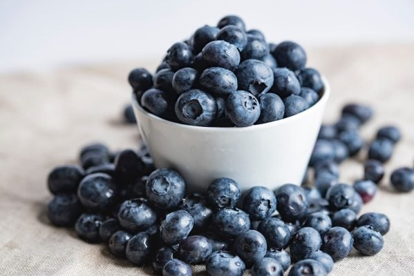 white bowl of blueberries overflowing