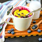 blueberry muffin mug cake with scattered blueberries and a glass of milk
