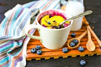 blueberry muffin mug cake in a small mug with a spoon and fresh blueberries and milk in the background