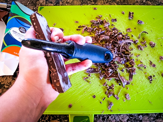 shaving a chocolate bar with a vegetable peeler for microwave cake topping