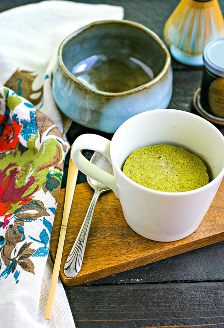 low carb mug cake made with matcha in front of mixing bowl and bamboo whisk