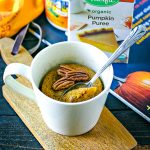 pumpkin mug cake topped with whole pecans with a silver spoon
