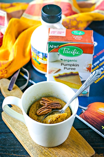 pumpkin mug cake in front of boxed pumpkin puree and maple syrup