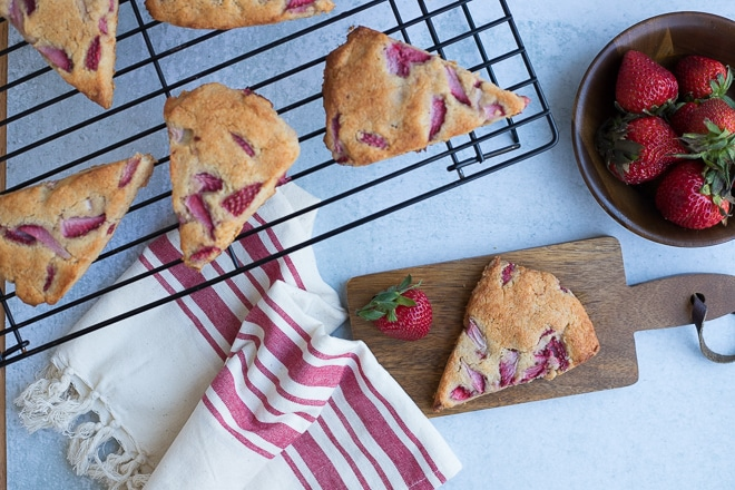 strawberry scones on a cooling rack with a bowl of fresh strawberries