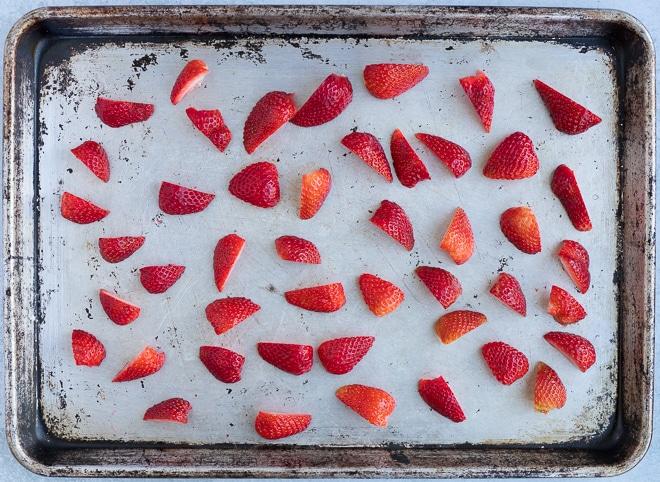 baking sheet of halved strawberries for roasting
