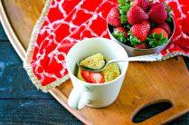 vanilla mug cake in a beige mug topped with sliced strawberries