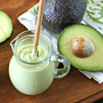 Avocado Crema in a glass jar with a wood spoon and cut avocado on a tray
