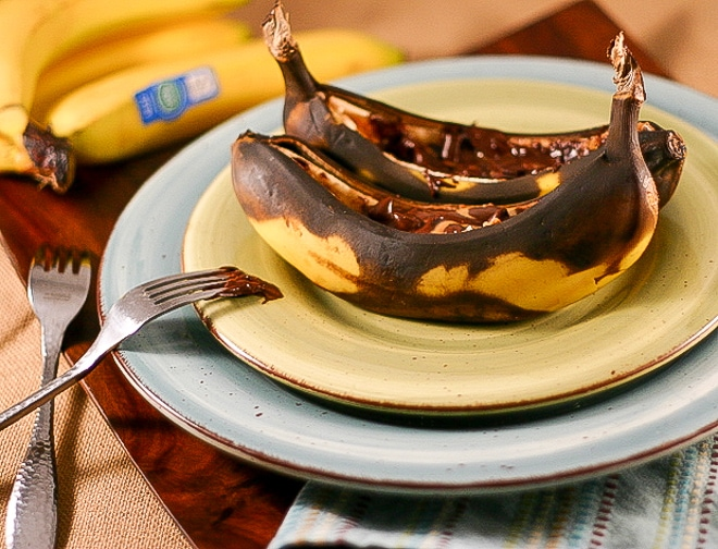 baked bananas on a plate topped with melted peanut butter and chocolate