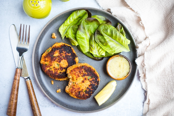overhead shot of cooked salmon cakes on a plate with lettuce, dipping sauce and lemon