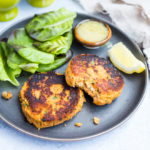grey plate of paleo salmon cakes with salad, lemon and dipping sauce