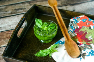 Vegan pesto in a small dish with fresh basil and wood spoon