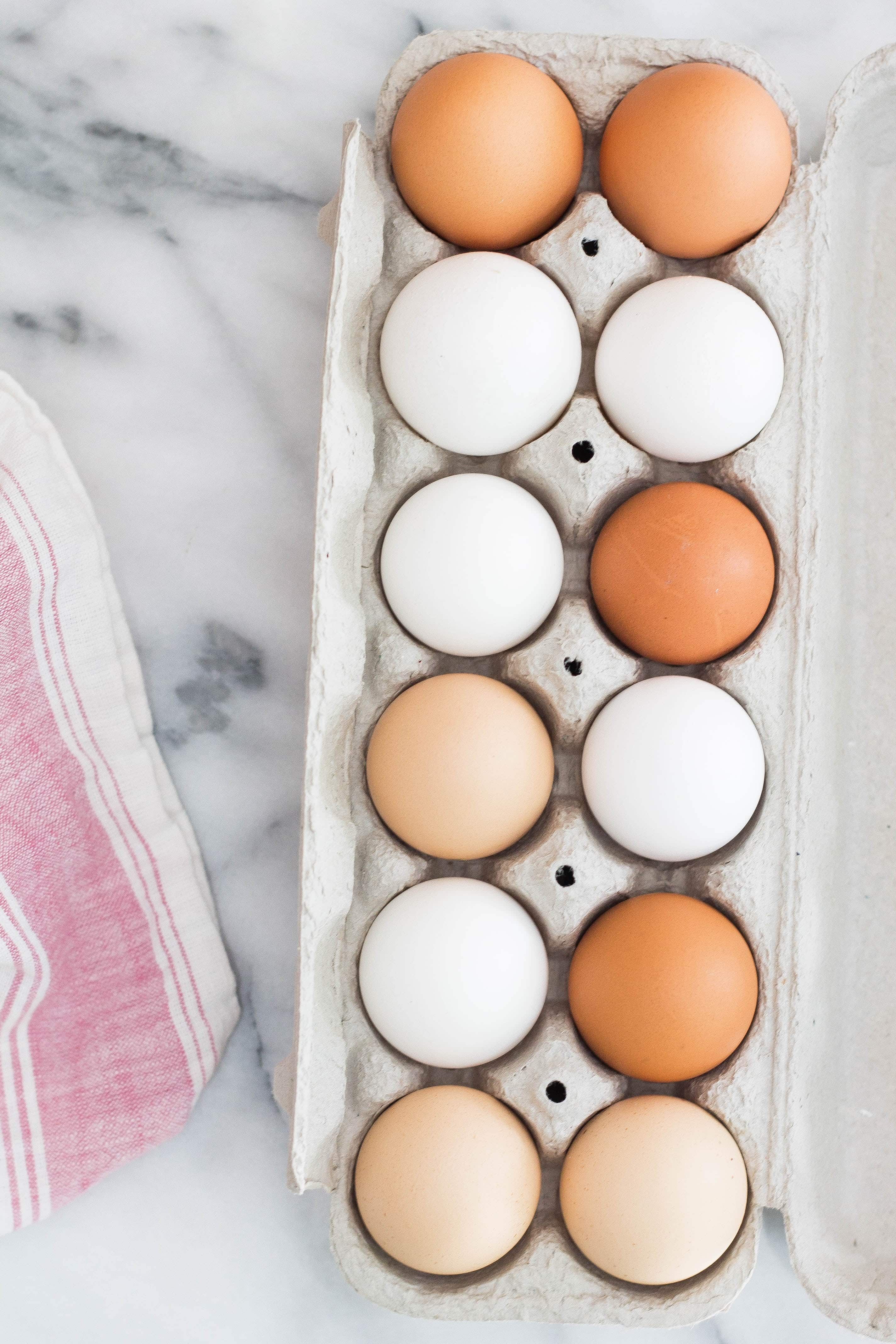 white and brown eggs in a container on a marble counter