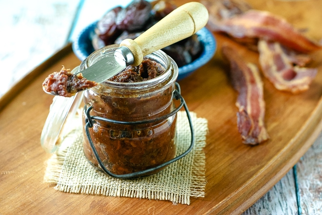 jar of homemade bacon jam in front of cooked bacon and medjool dates