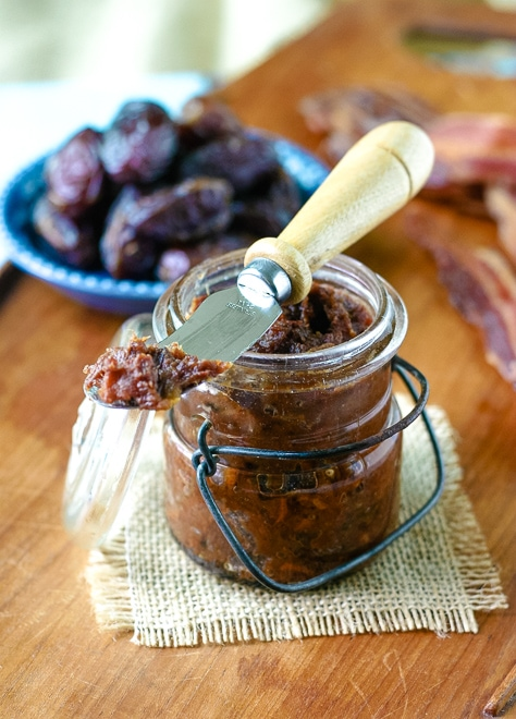 clear jar filled with bacon jam in front of bowl of medjool dates