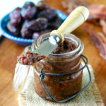 close up of bacon jam in a jar in front of small bowl of medjool dates