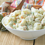 close up of potato salad in a white serving bowl