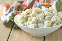 white bowl of classic potato salad on a wood table