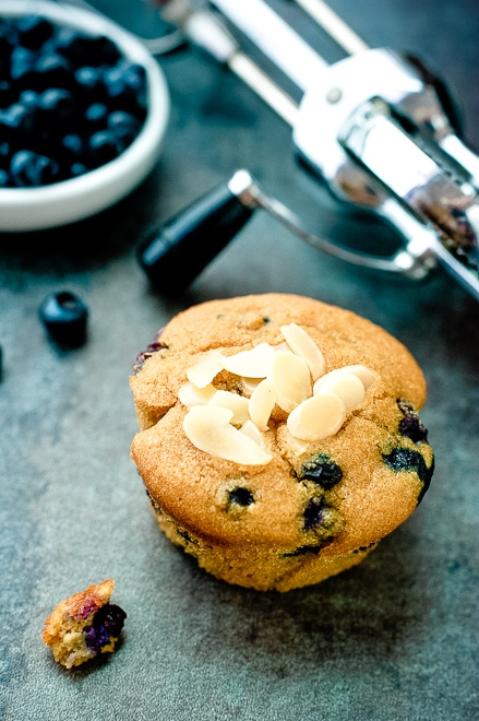 one blueberry muffin with crumbs around it and a bowl of fresh blueberries
