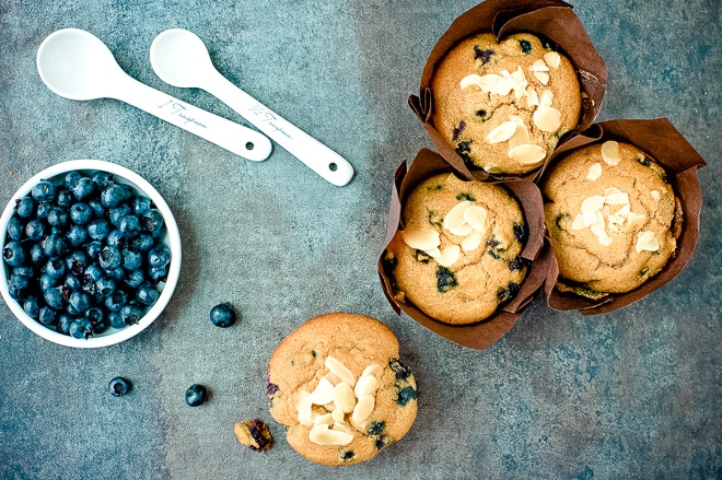 cooked gluten-free blueberry muffins on a counter with fresh blueberries and measuring spoons
