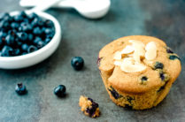 paleo blueberry muffin on a counter with fresh blueberries