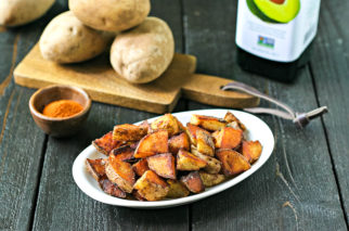 plate of home fries in front of avocado oil and potaotes