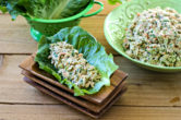 Tuna Salad in a romaine lettuce leaf in front of a bowl of more tuna salad