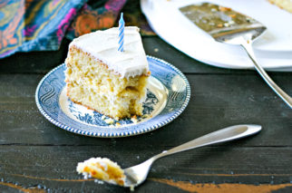 small blue plate with single piece of gluten free cake topped with birthday candle