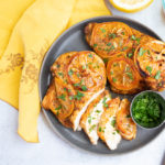 overhead photo of baked lemon chicken breast on a grey plate topped with parsley