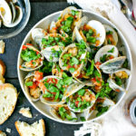 close up of steamed clams recipe in white bowl with bread on the side